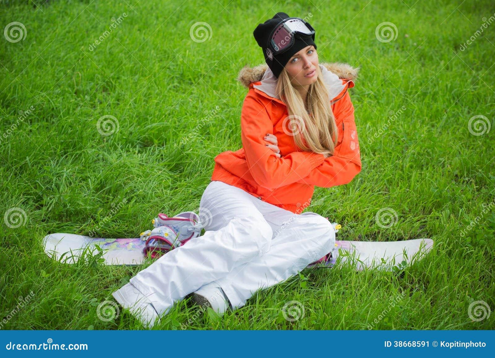 Το κορίτσι με ένα σνόουμπορντ κάθεται στη χλόη