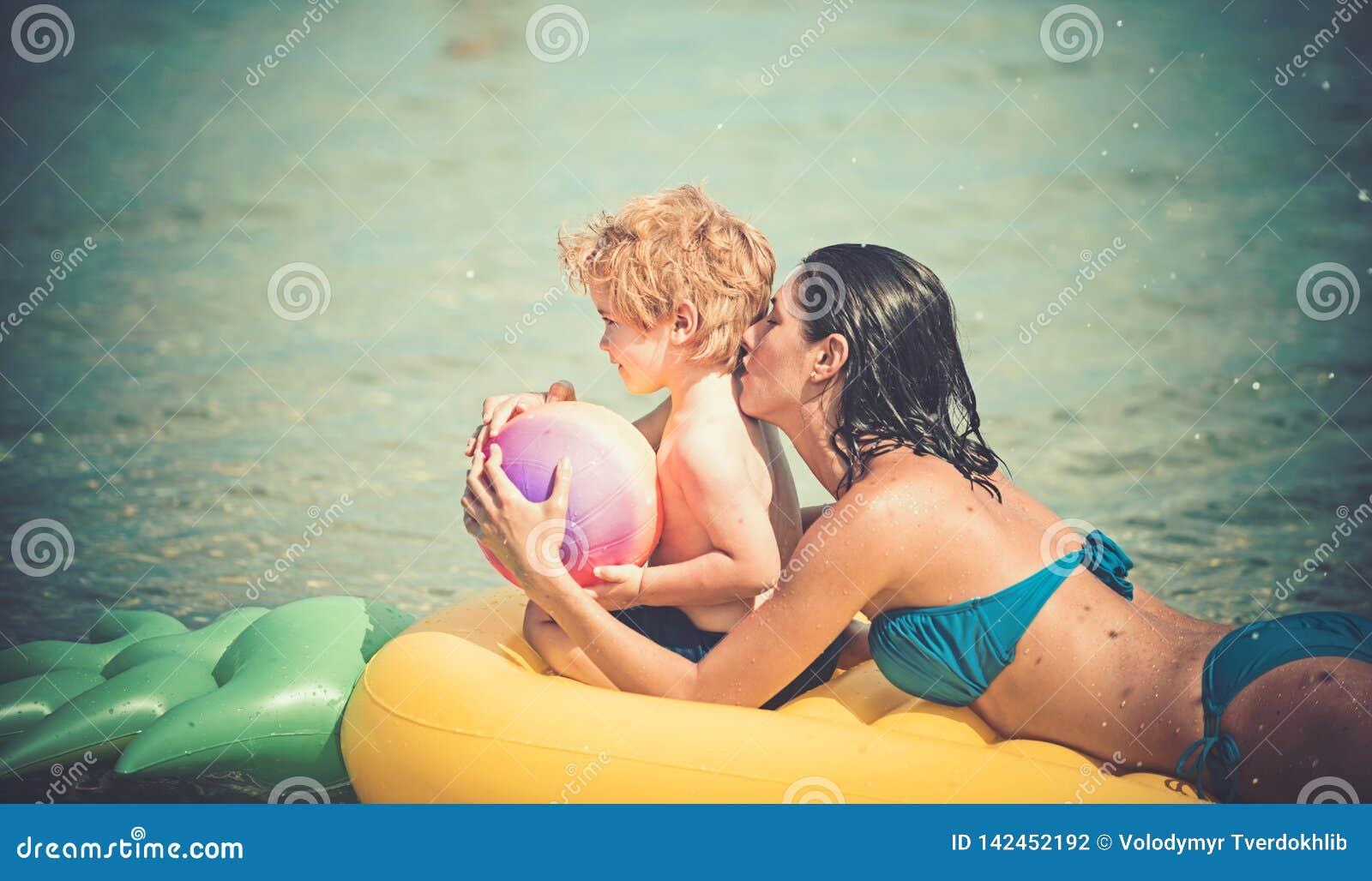 Το κορίτσι με το παιδί μικρών παιδιών κολυμπά στο κίτρινο στρώμα αέρα στο νερό το καλοκαίρι