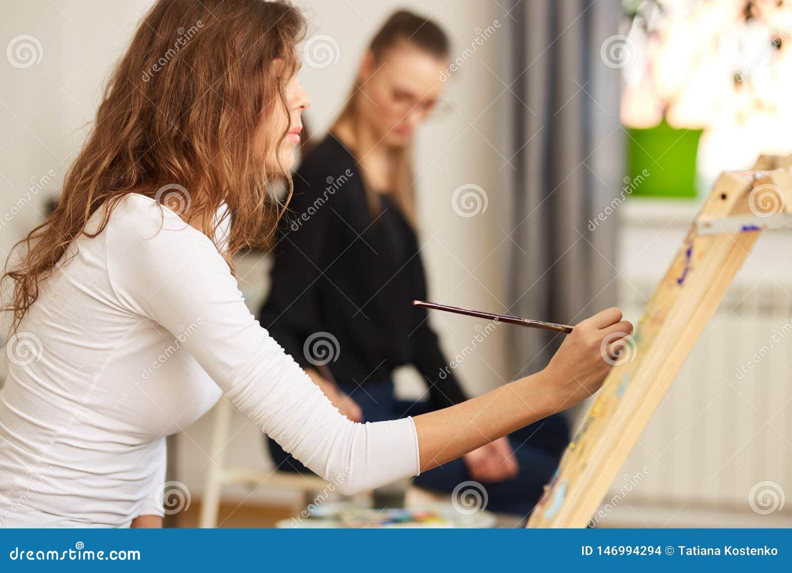 Το κορίτσι με την καφετιά σγουρή τρίχα που ντύνεται στην άσπρη μπλούζα χρωματίζει μια εικόνα easel στο σχολείο σχεδίων