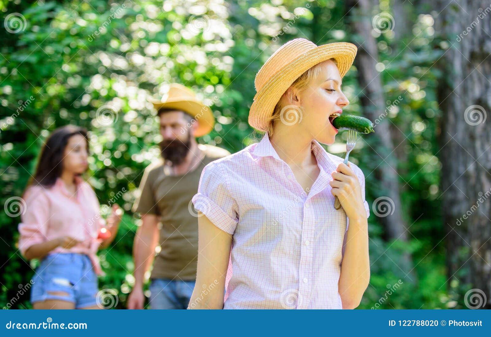 Το κορίτσι με τη μεγάλη όρεξη τρώει τα ψημένα τρόφιμα Φίλοι που τρώνε το πικ-νίκ τροφίμων Άτομο που ταΐζει την πεινασμένη κυρία μ