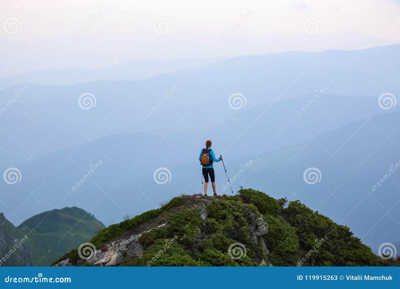 Το κορίτσι με τον τουριστικό εξοπλισμό πηγαίνει επάνω στην αιχμή του δύσκολου υψηλού λόφου με το χορτοτάπητα Το τοπίο των βουνών