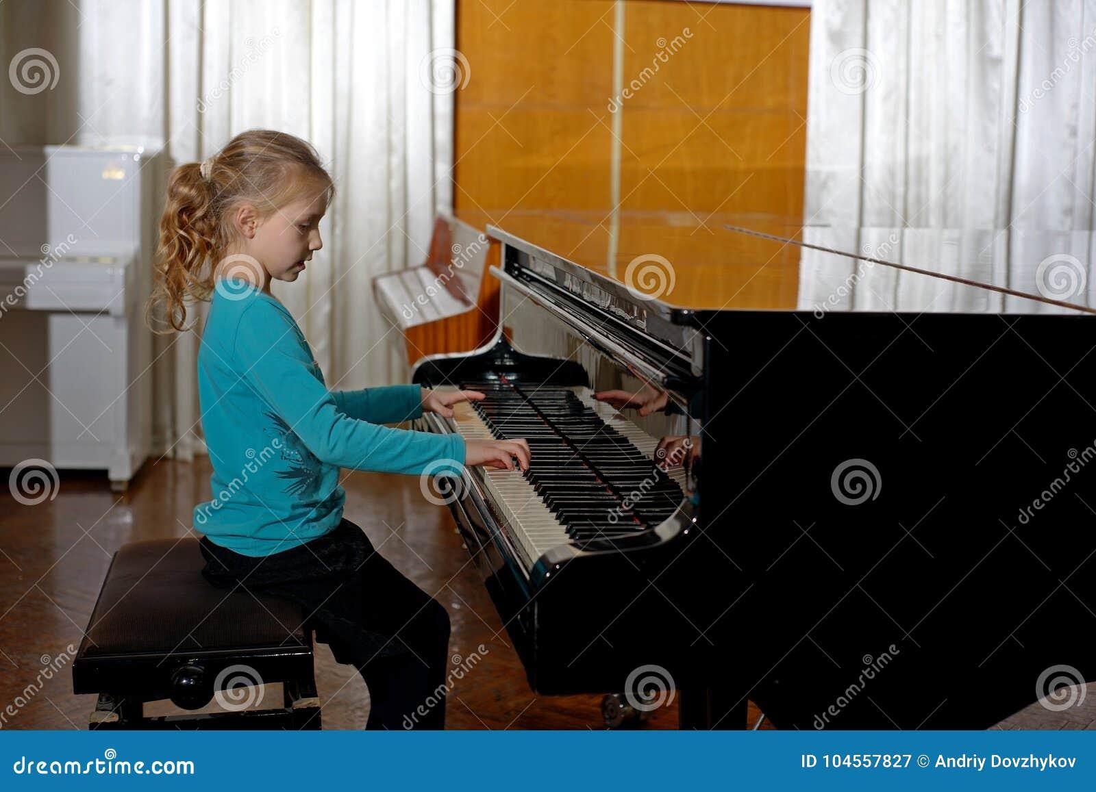 Το κορίτσι παίζει το πιάνο, κλείνει επάνω, άσπρο και μαύρο πληκτρολόγιο