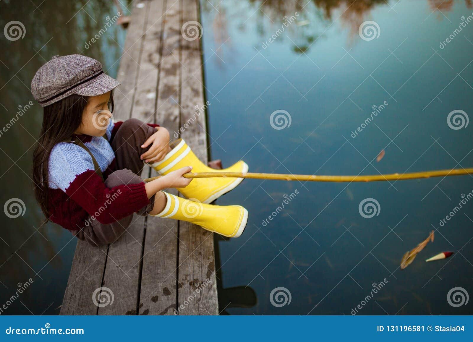 Το κορίτσι παιδιών κάθεται στην ξύλινη γέφυρα αλιείας και πιάνει τα ψάρια με το s