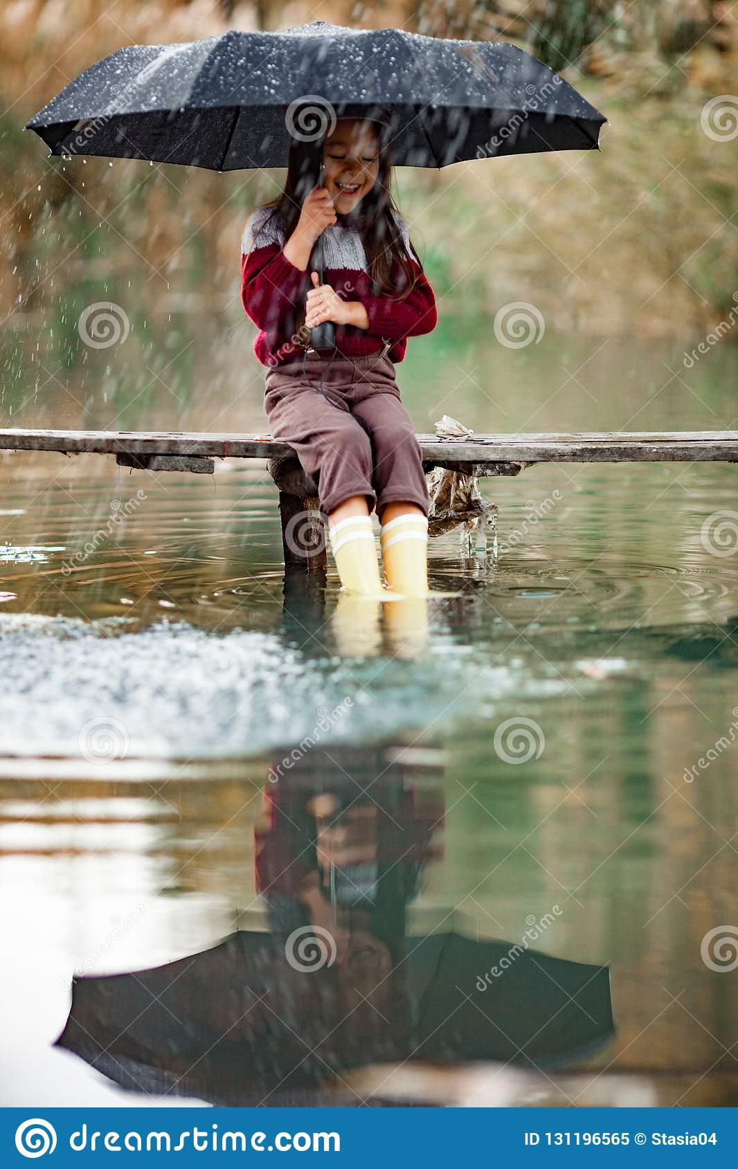 Το κορίτσι παιδιών με την ομπρέλα κάθεται στην ξύλινη γέφυρα και laughes στο RA