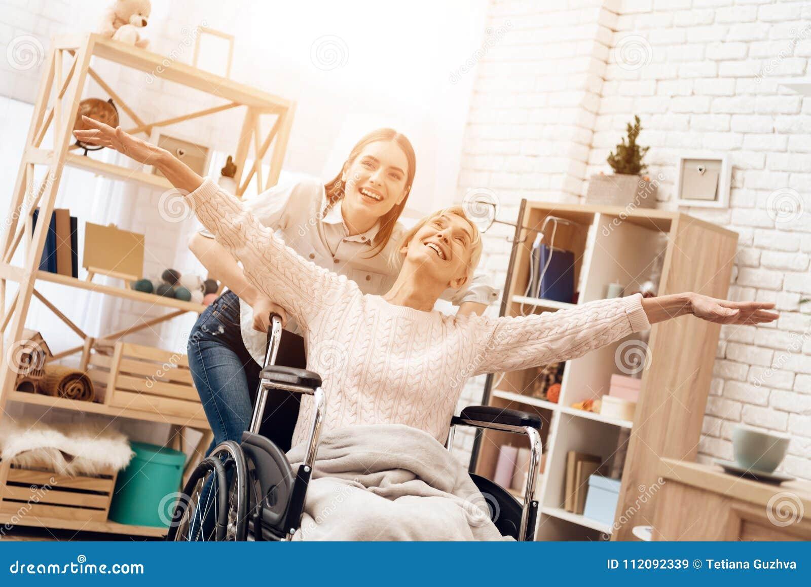 Το κορίτσι περιποιείται την ηλικιωμένη γυναίκα στο σπίτι Το κορίτσι οδηγά τη γυναίκα στην αναπηρική καρέκλα Η γυναίκα αισθάνεται