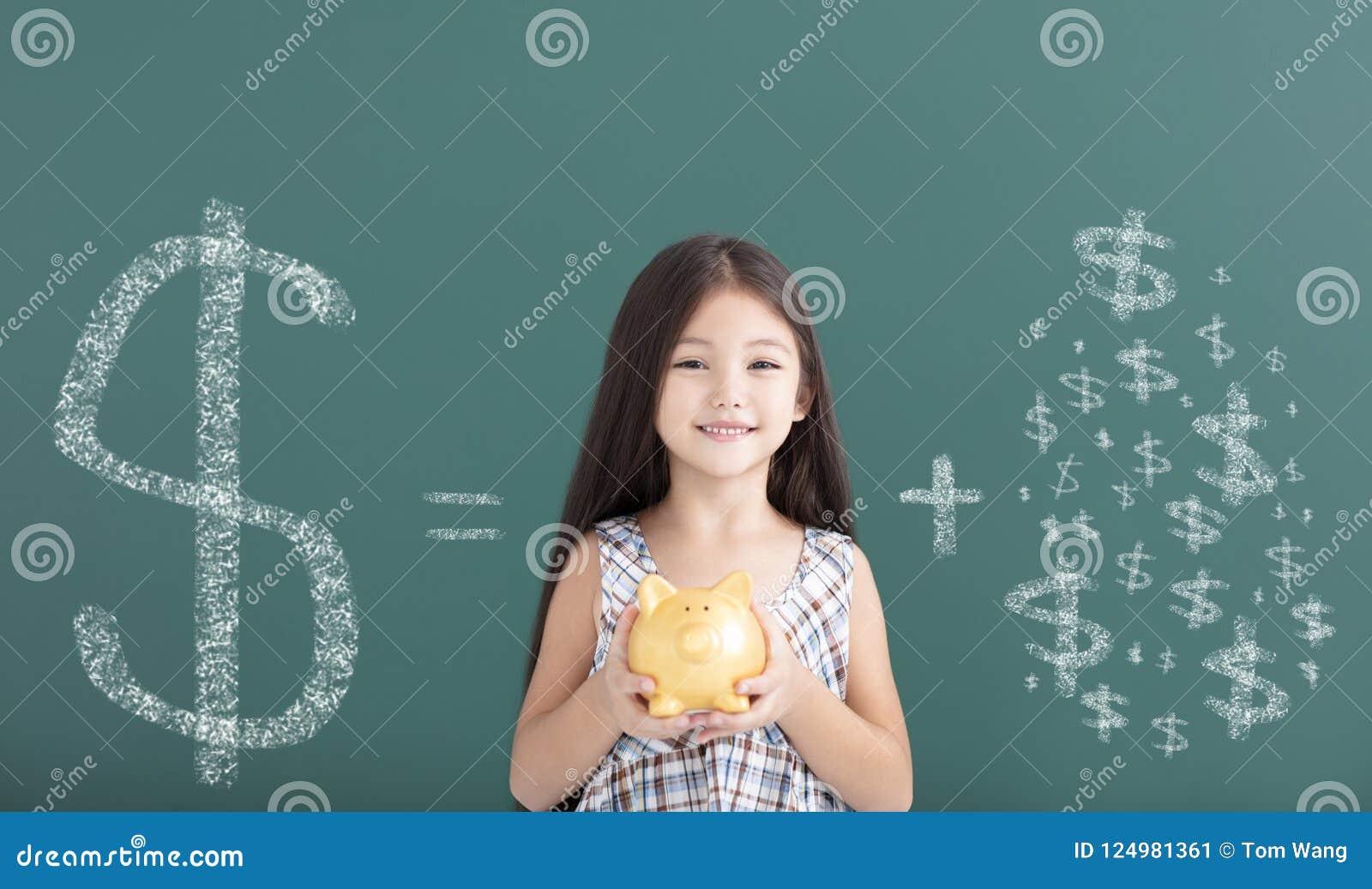 το κορίτσι που κρατά τη piggy τράπεζα και σώζει την έννοια χρημάτων