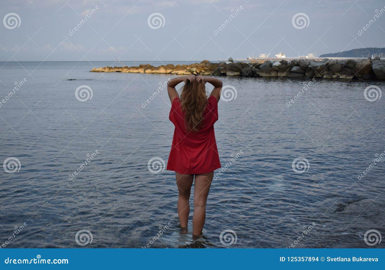Το κορίτσι στο κόκκινο στέκεται στην παραλία και αγγίζει την τρίχα της