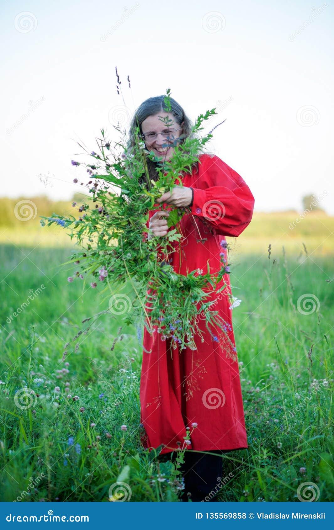 Το κορίτσι στο κόκκινο φόρεμα κάνει ένα στεφάνι της χλόης και των άγριων λουλουδιών στο υπόβαθρο ενός πράσινου λιβαδιού