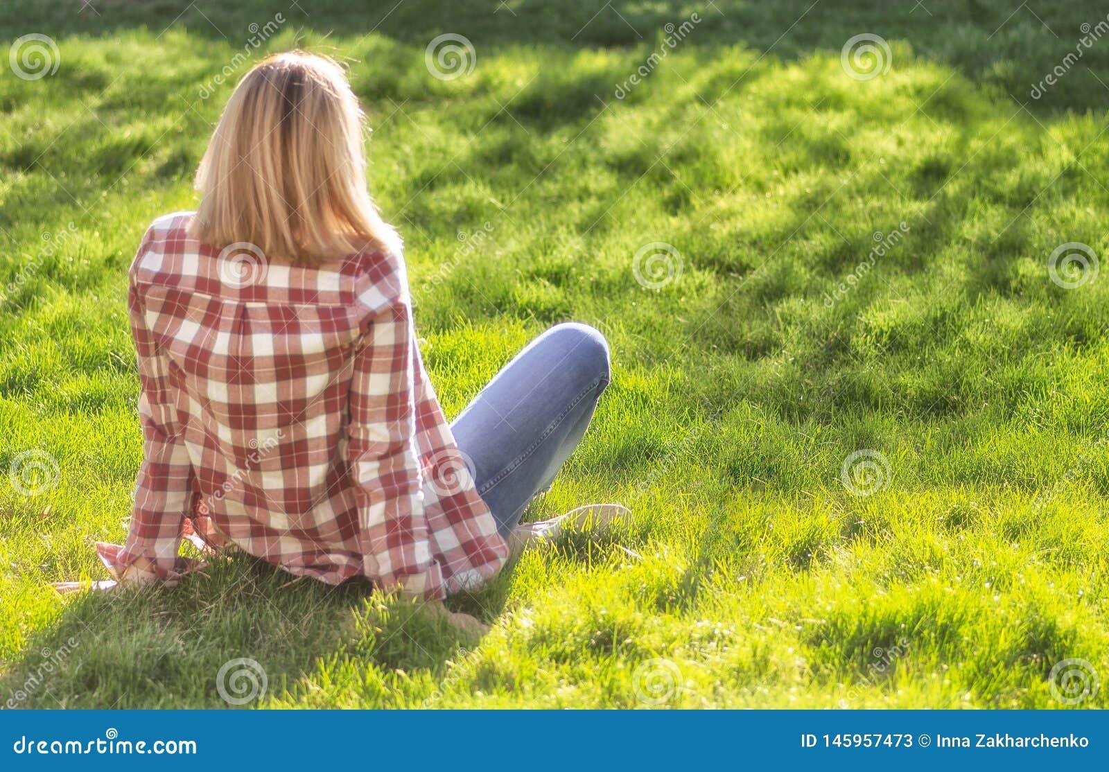 Το κορίτσι χαλαρώνει στο λιβάδι Η ξανθή όμορφη νέα γυναίκα κάθεται στη χλόη και απολαμβάνει τον ήλιο Υπαίθριος r Φθορά