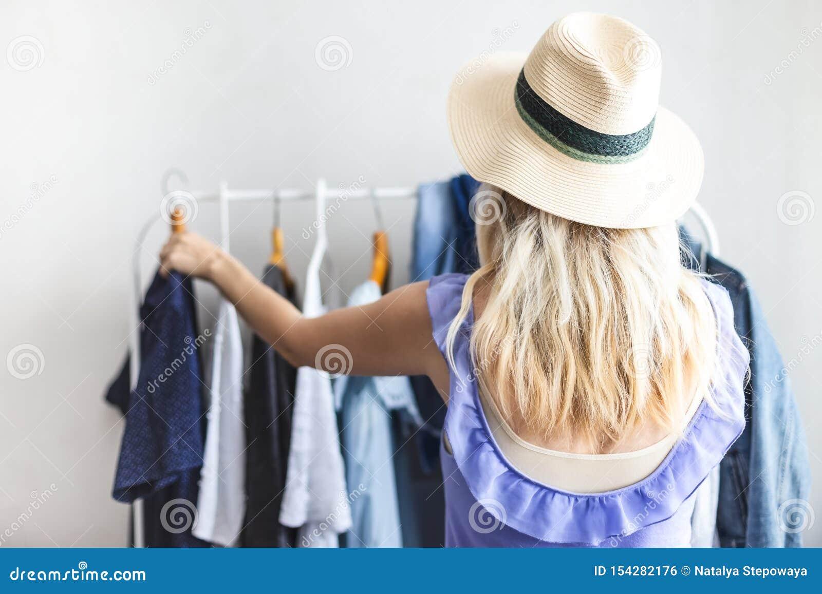 Το κορίτσι Blondy κοντά σε μια ντουλάπα με τα ενδύματα δεν μπορεί να επιλέξει τι να φορέσει