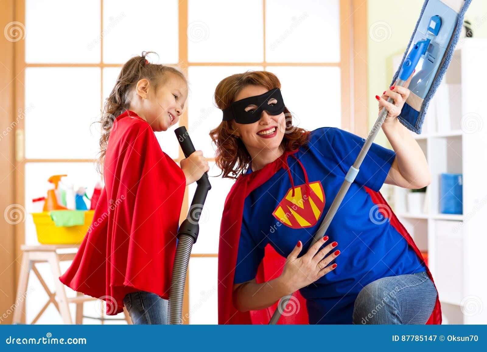Το κορίτσι Preschooler και η μητέρα της έντυσαν όπως τα superheroes Μέσης ηλικίας γυναίκα και παιδί που παίζουν κάνοντας τον καθα