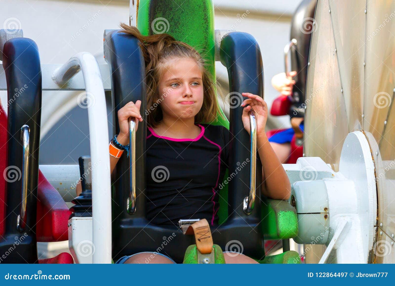 Το κορίτσι PreTeen φαίνεται είτε βαριεστημένο είτε Naseous σε μια γρήγορη περιστροφή Ri