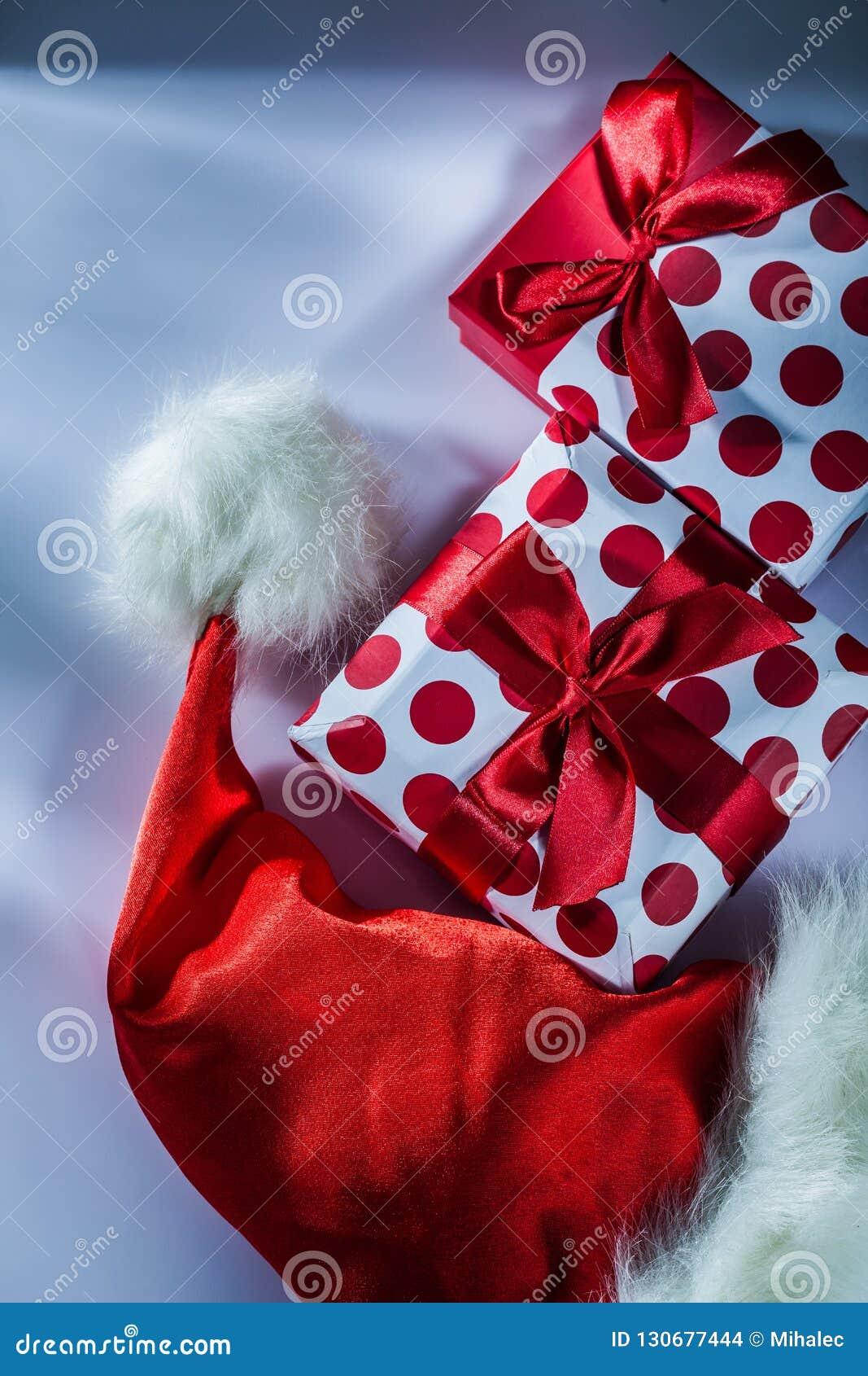Το κόκκινο καπέλο Santa συσκεύασε το παρόν κιβώτιο στο άσπρο υπόβαθρο