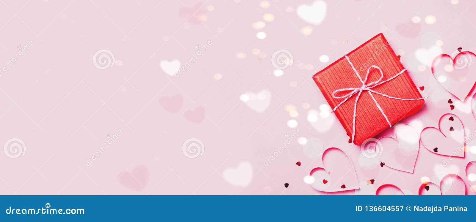 Το κόκκινο τόξο κιβωτίων 6ος δώρων και ακτινοβολεί σπινθηρίσματα στο ρόδινο υπόβαθρο Έννοια ημέρας βαλεντίνων ` s του ST