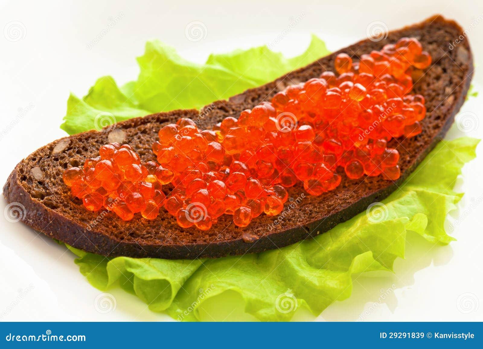 Το κόκκινο χαβιάρι, είναι στο ψωμί σε μια πράσινη σαλάτα φύλλων