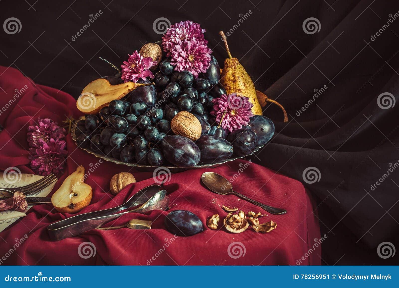 Το κύπελλο φρούτων με τα σταφύλια και τα δαμάσκηνα ενάντια σε ένα καφέ τραπεζομάντιλο