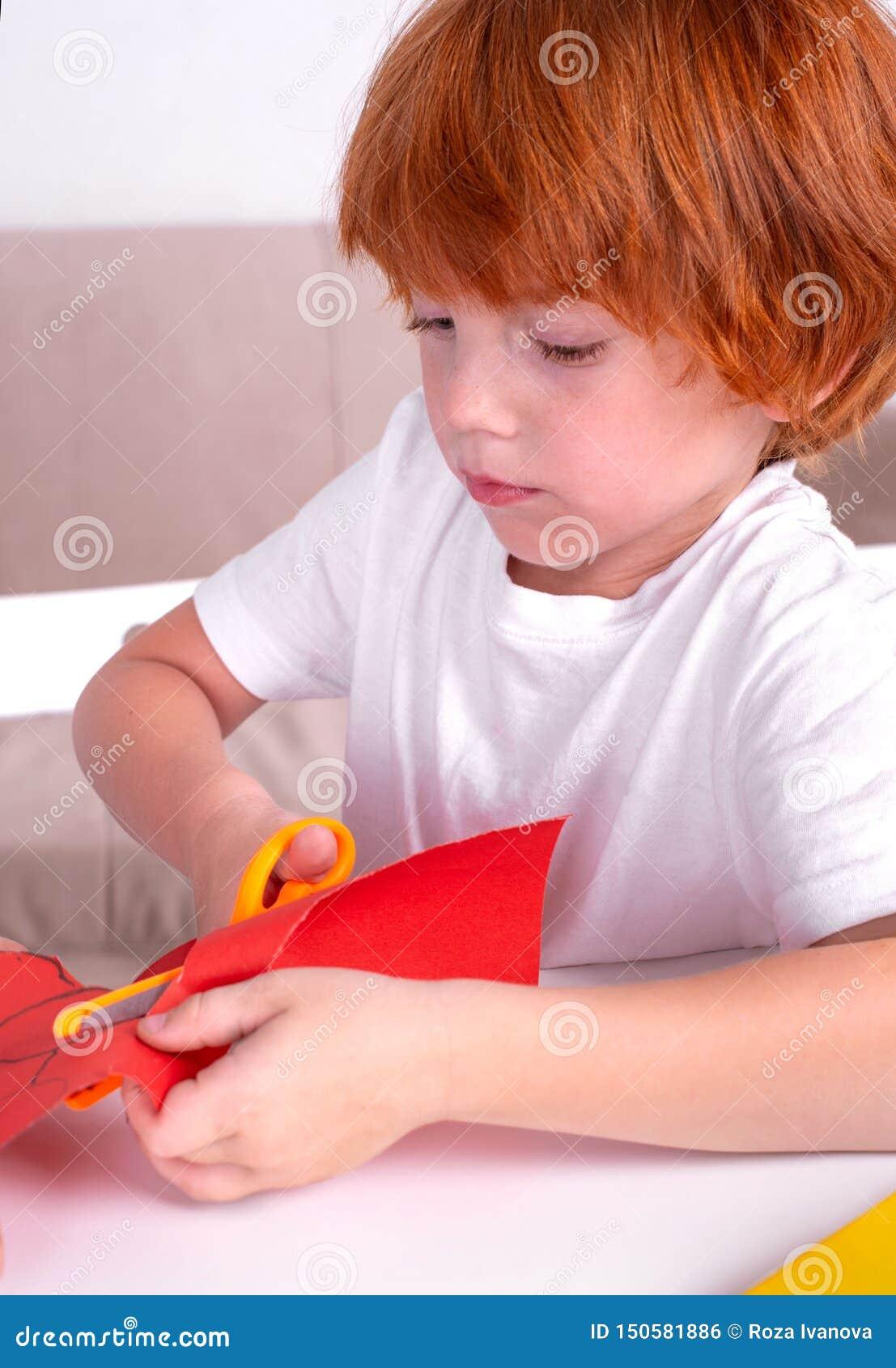 Το λίγο κοκκινομάλλες αγόρι κάθεται στον πίνακα και αποκόπτει του χρωματισμένου εγγράφου με το ψαλίδι Μαθαίνει και αναπτύσσεται