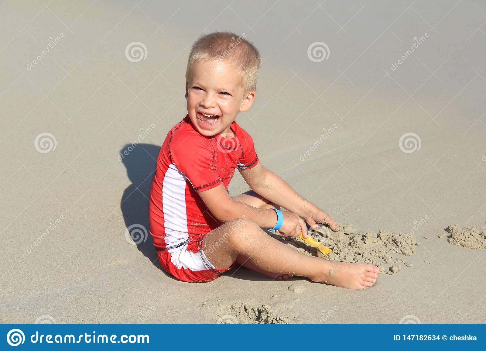 Το λίγο ξανθό αγόρι στα ενδύματα με το UV φίλτρο παίζει με την άμμο στην παραλία θαλασσίως, διακοπές με τα παιδιά, που προστατεύο