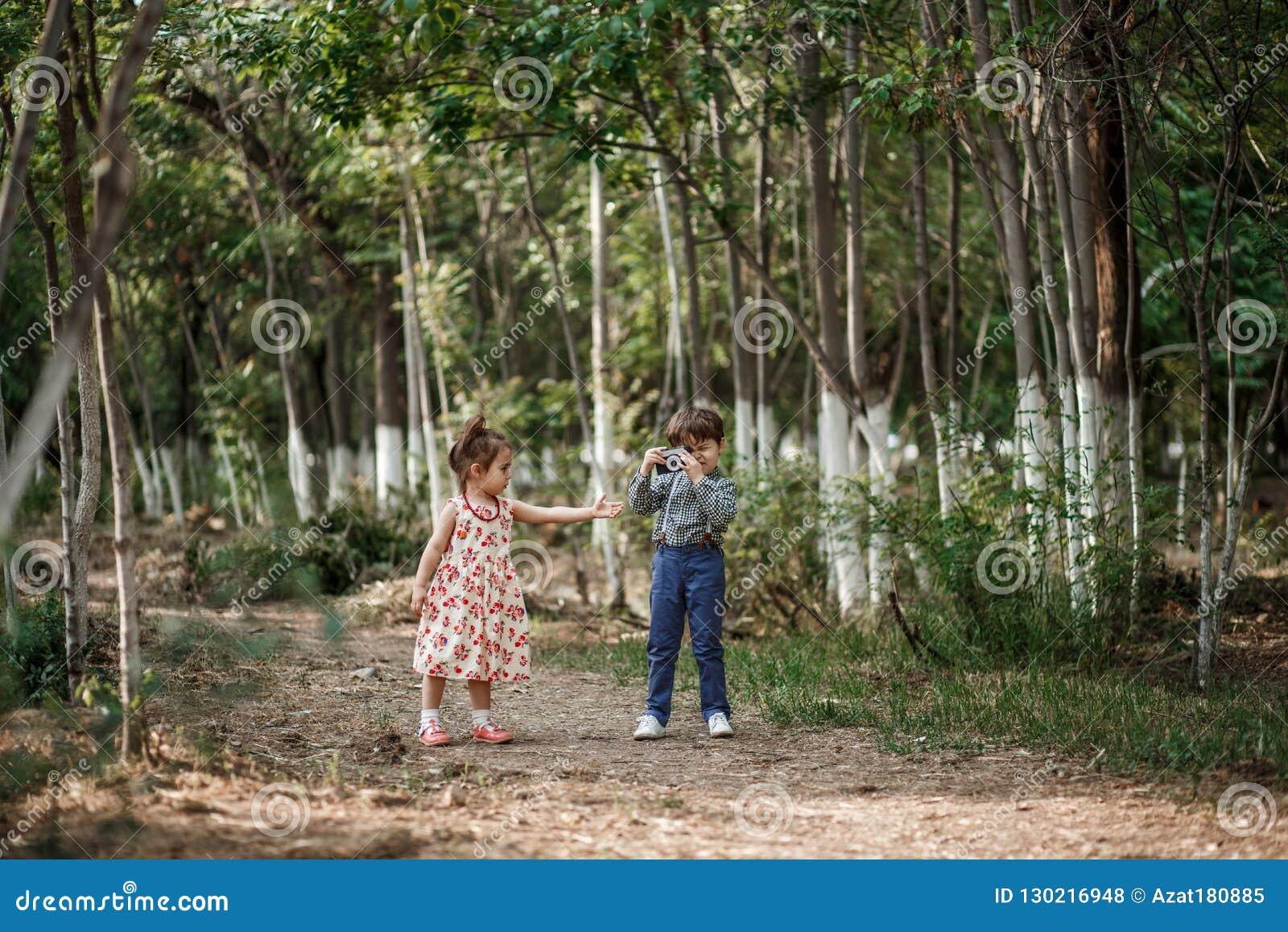 Το λίγο χαριτωμένο αγόρι στα εκλεκτής ποιότητας ενδύματα και το λίγο όμορφο κορίτσι σε ένα αναδρομικό φόρεμα περπατούν στα ξύλα κ