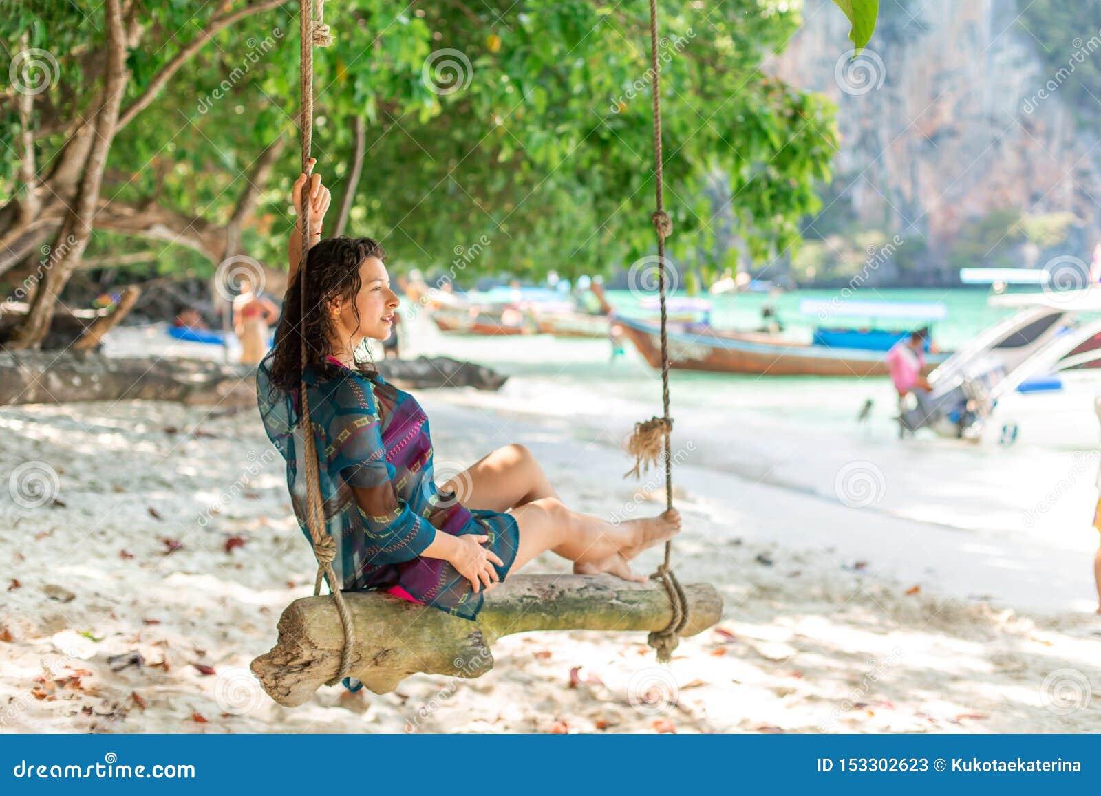 Το λεπτό προκλητικό πρότυπο κοριτσιών σε μια τοποθέτηση μαγιό σε μια ξύλινη ταλάντευση έδεσε σε ένα δέντρο Στο υπόβαθρο της παραλ