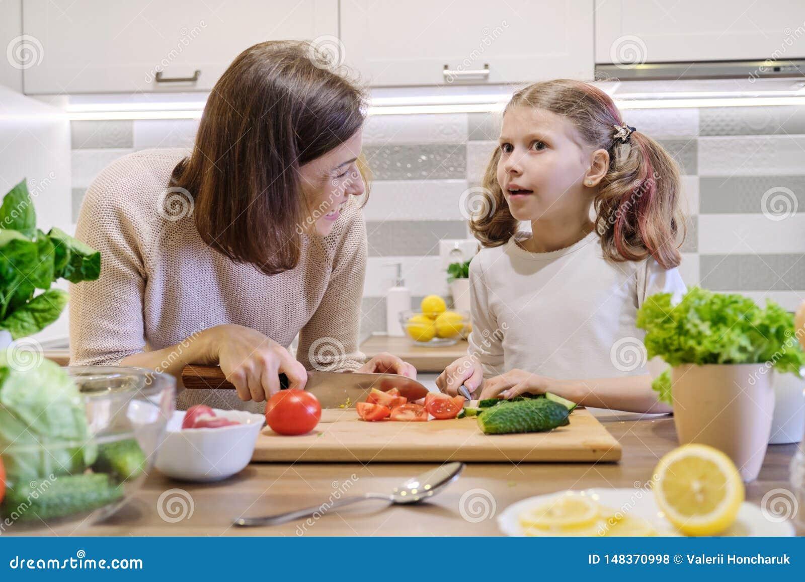 Το μαγείρεμα μητέρων και κορών μαζί σαλάτα, το γονέα και το παιδί κουζινών στη φυτική μιλά το χαμόγελο