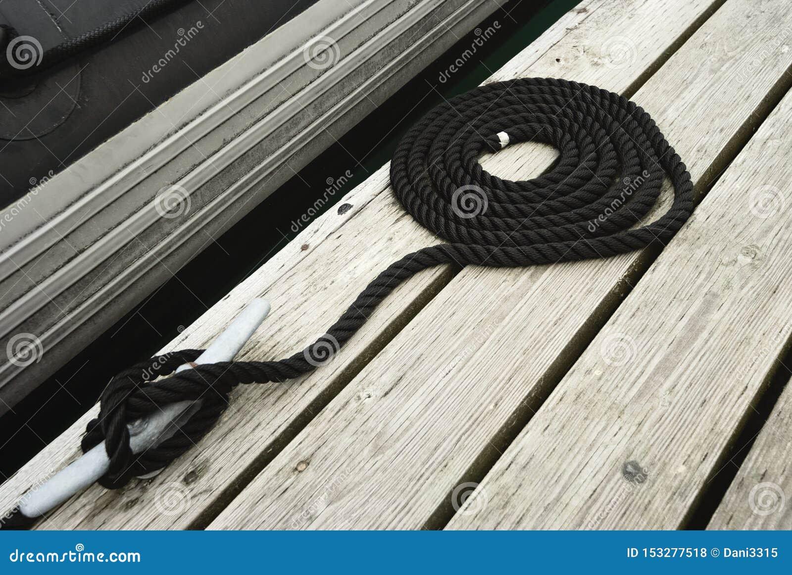 Το μαύρο στροβιλισμένο δένοντας σχοινί ενέπλεξε σε ένα Bitt εξασφαλίζοντας τη βάρκα στο λιμενοβραχίονα