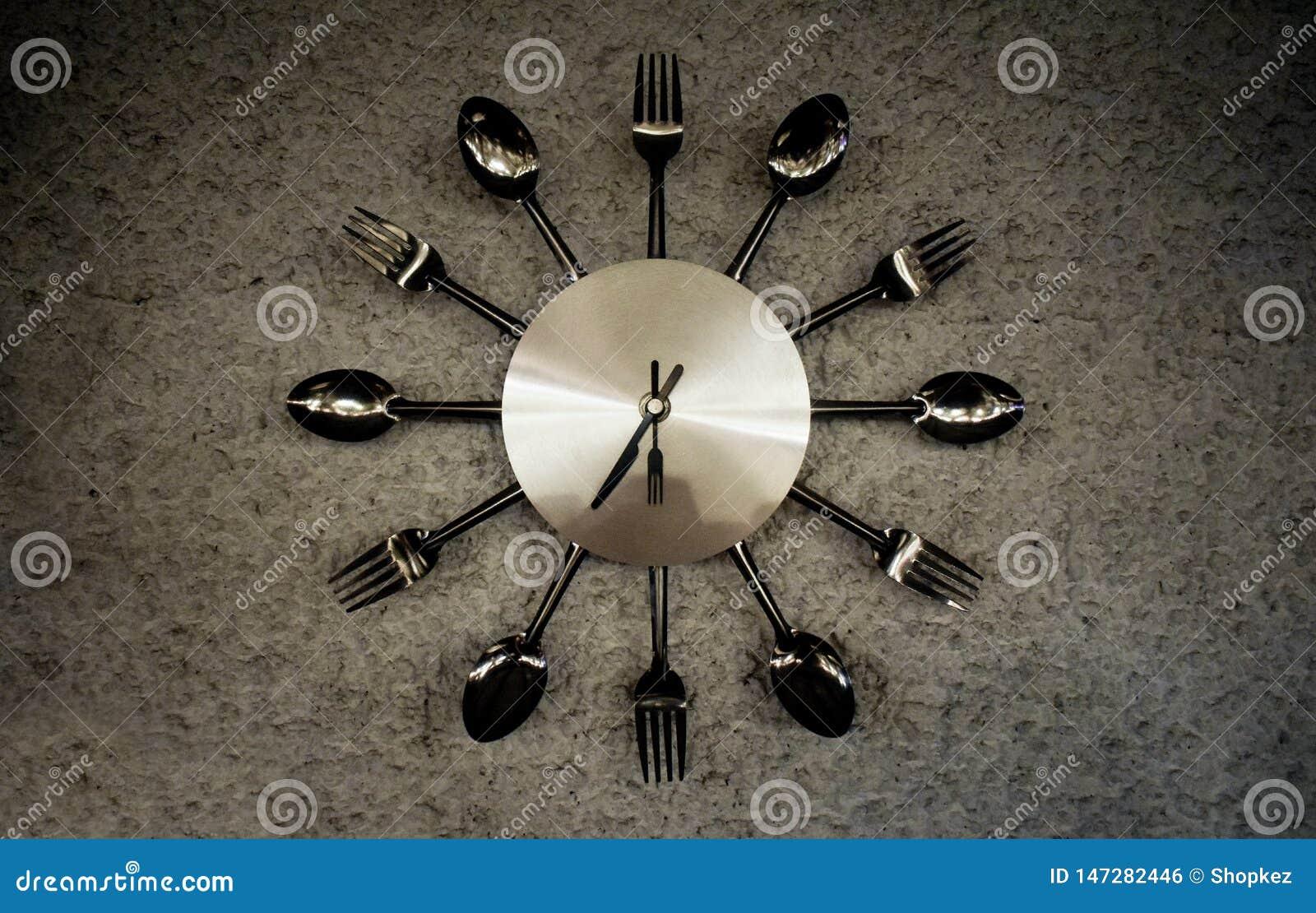 Το μεταλλικό λάμποντας ρολόι έκανε ειδικά για τη διακόσμηση εστιατορίων με τα δίκρανα, κουτάλια και knifes