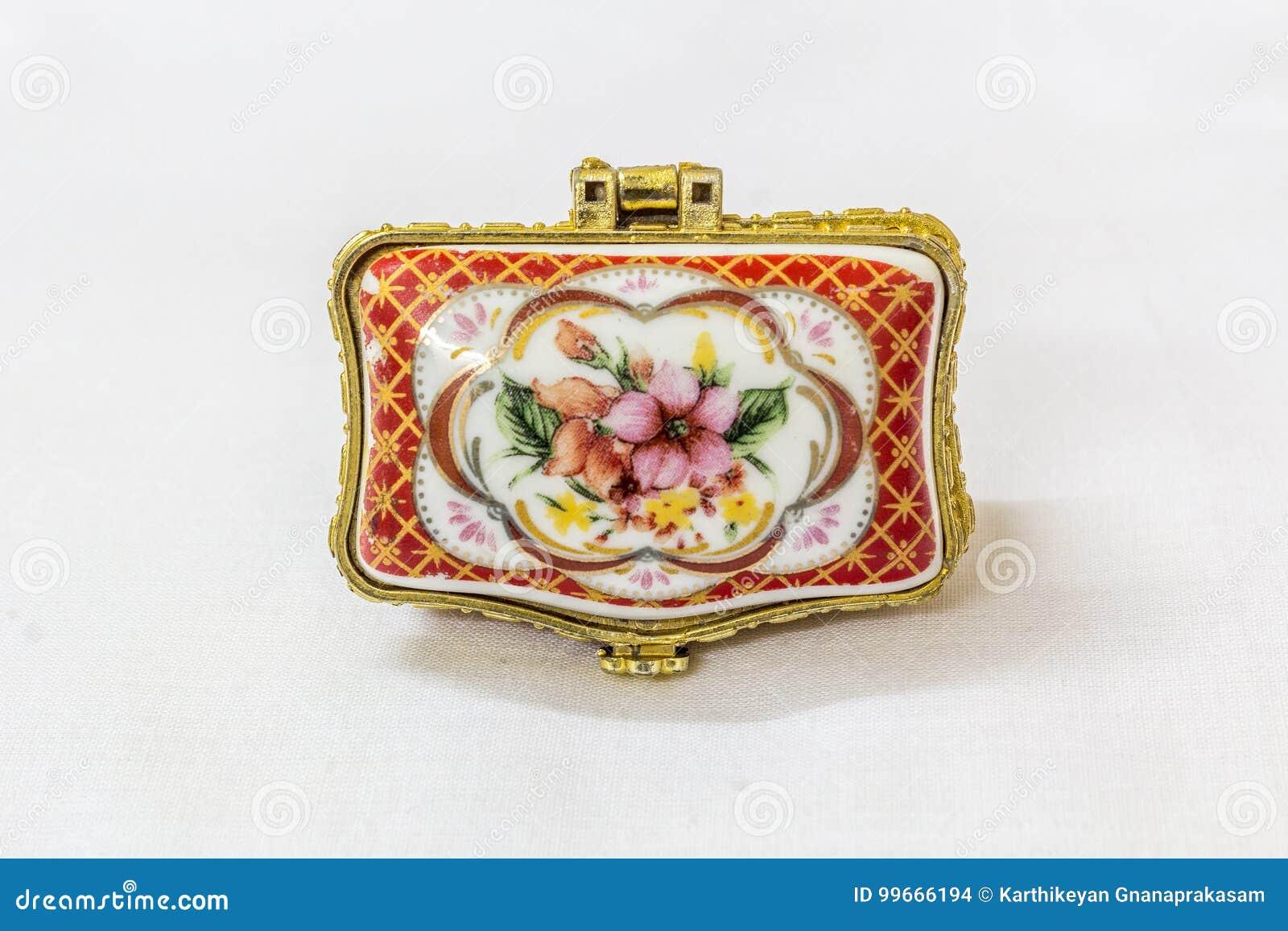 Το μικροσκοπικό ζωηρόχρωμο κιβώτιο κοσμημάτων με το χρυσό crimp σε ένα άσπρο υπόβαθρο Μακροεντολή με το εξαιρετικά ρηχό βάθος του