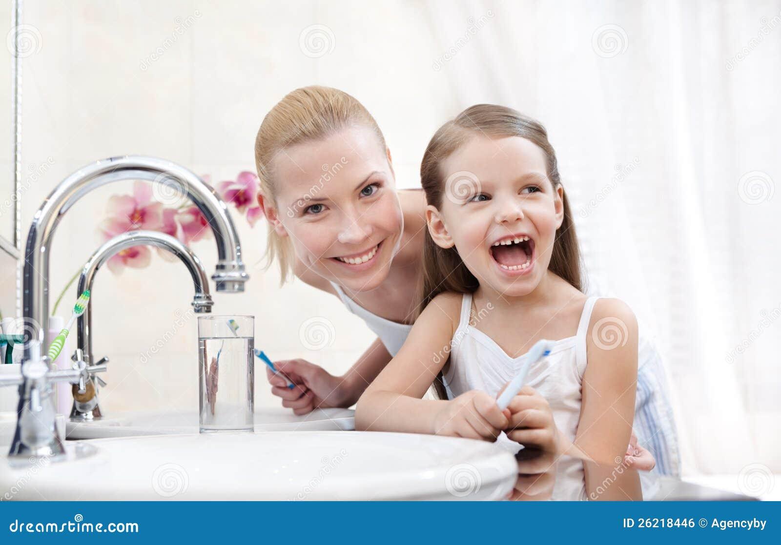 Το μικρό κορίτσι βουρτσίζει τα δόντια με τη μητέρα της