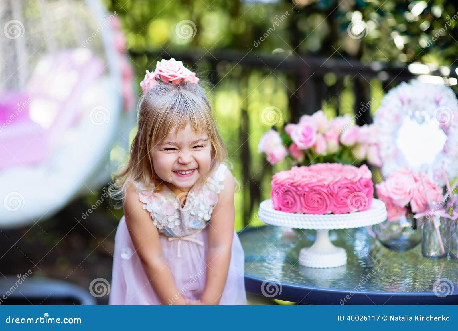 Το μικρό κορίτσι γιορτάζει χρόνια πολλά το κόμμα με ροδαλό υπαίθριο