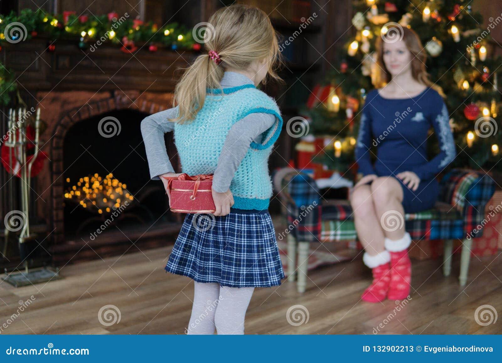 Το μικρό κορίτσι δίνει mom ένα δώρο δίπλα σε ένα χριστουγεννιάτικο δέντρο με ένα χρυσό bokeh