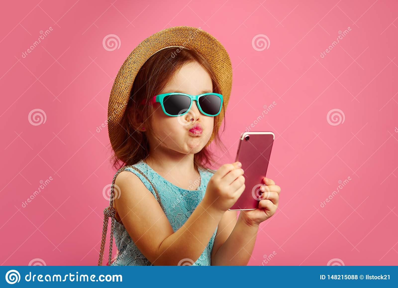 Το μικρό κορίτσι κάνει ένα πορτρέτο selfie στο τηλέφωνο, τραβά τα χείλια της στη κάμερα, φορά ένα καπέλο αχύρου και τα γυαλιά ηλί