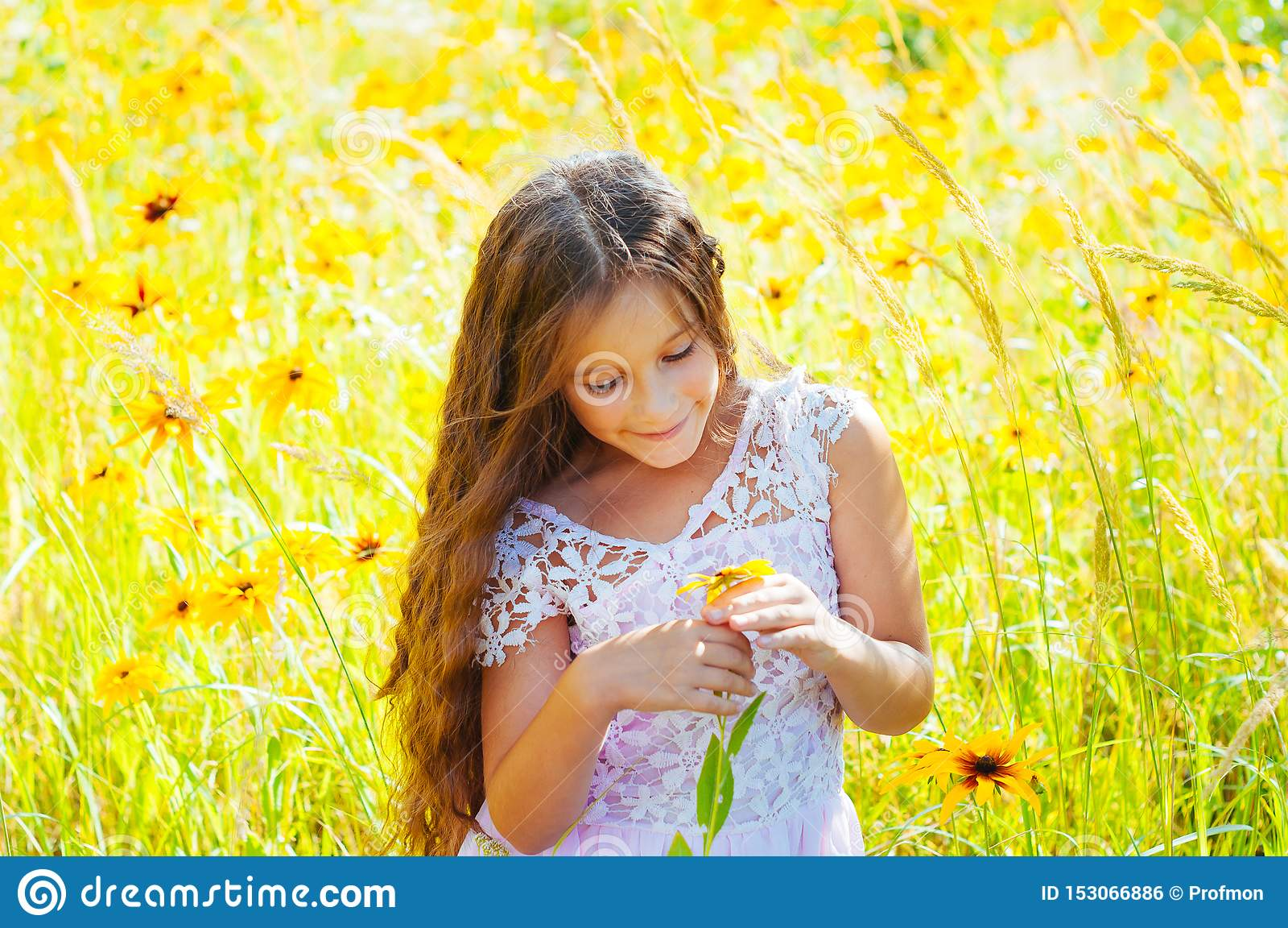 Το μικρό κορίτσι με μακρυμάλλη σε ένα άσπρο φόρεμα χαίρεται για έναν τομέα με τα λουλούδια