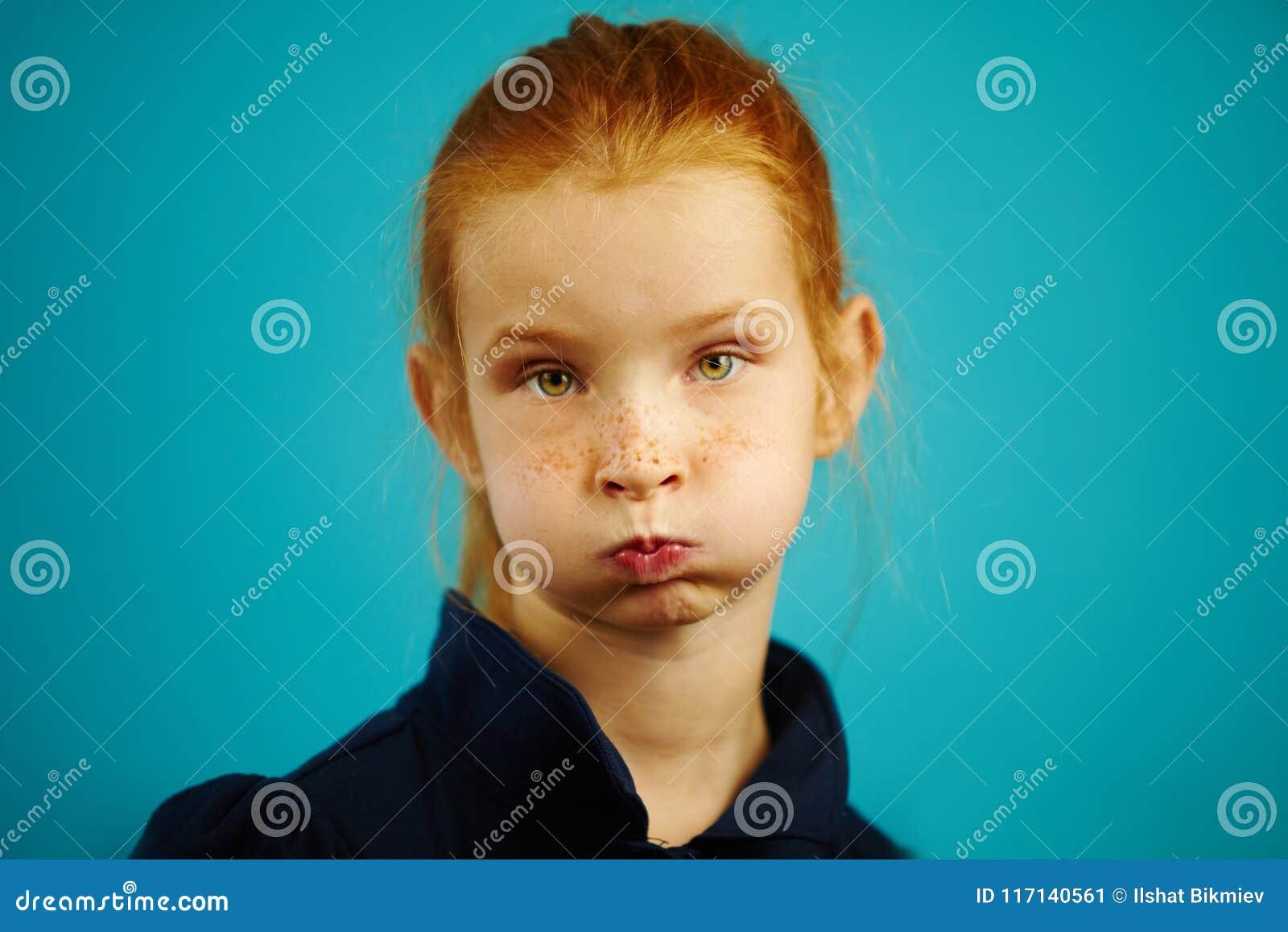 Το μικρό κορίτσι με το pouty στόμα και έκπληκτος φαίνεται απομονωμένο στο μπλε υπόβαθρο