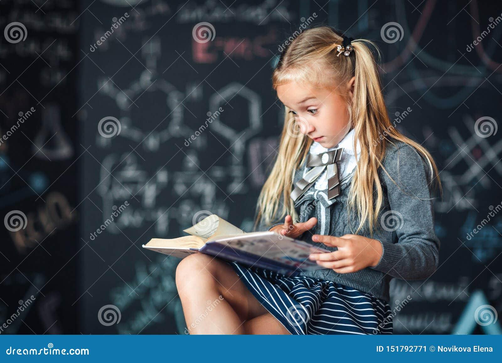 Το μικρό κορίτσι ξανθό στη σχολική στολή εξετάζει το βιβλίο με ένα έκπληκτο πρόσωπο Πίνακας κιμωλίας με τους σχολικούς τύπους Σύν