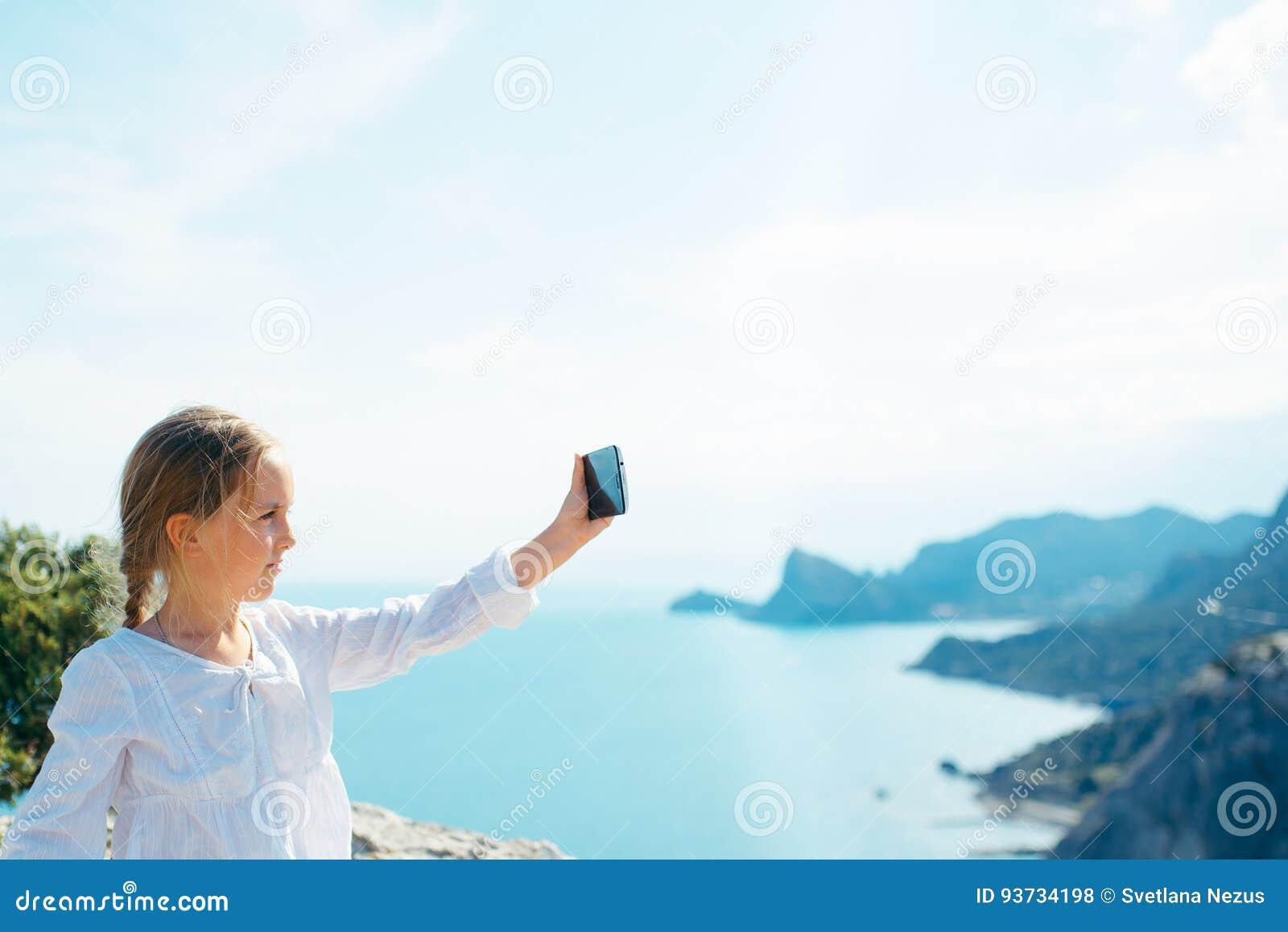 Το μικρό κορίτσι παίρνει την εικόνα στο smartphone