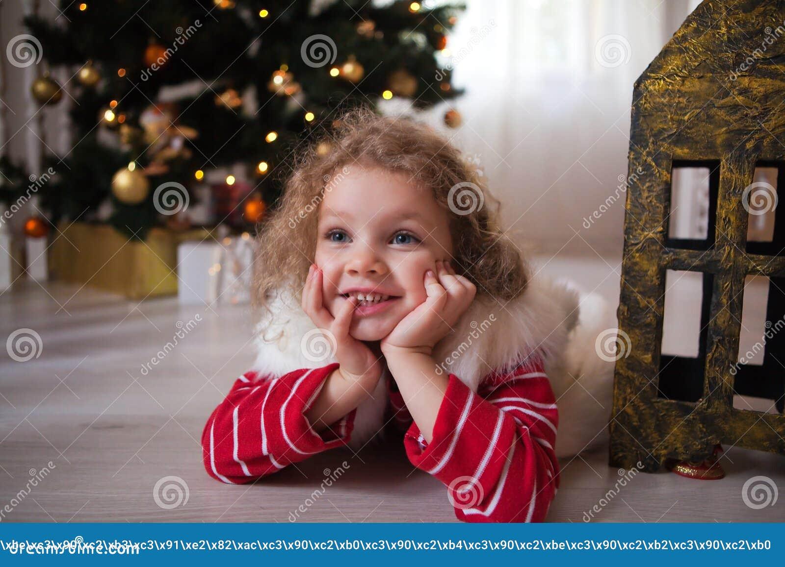 Το μικρό κορίτσι στο κόκκινο πουλόβερ βρίσκεται κάτω από το χριστουγεννιάτικο δέντρο και περιμένει ένα θαύμα