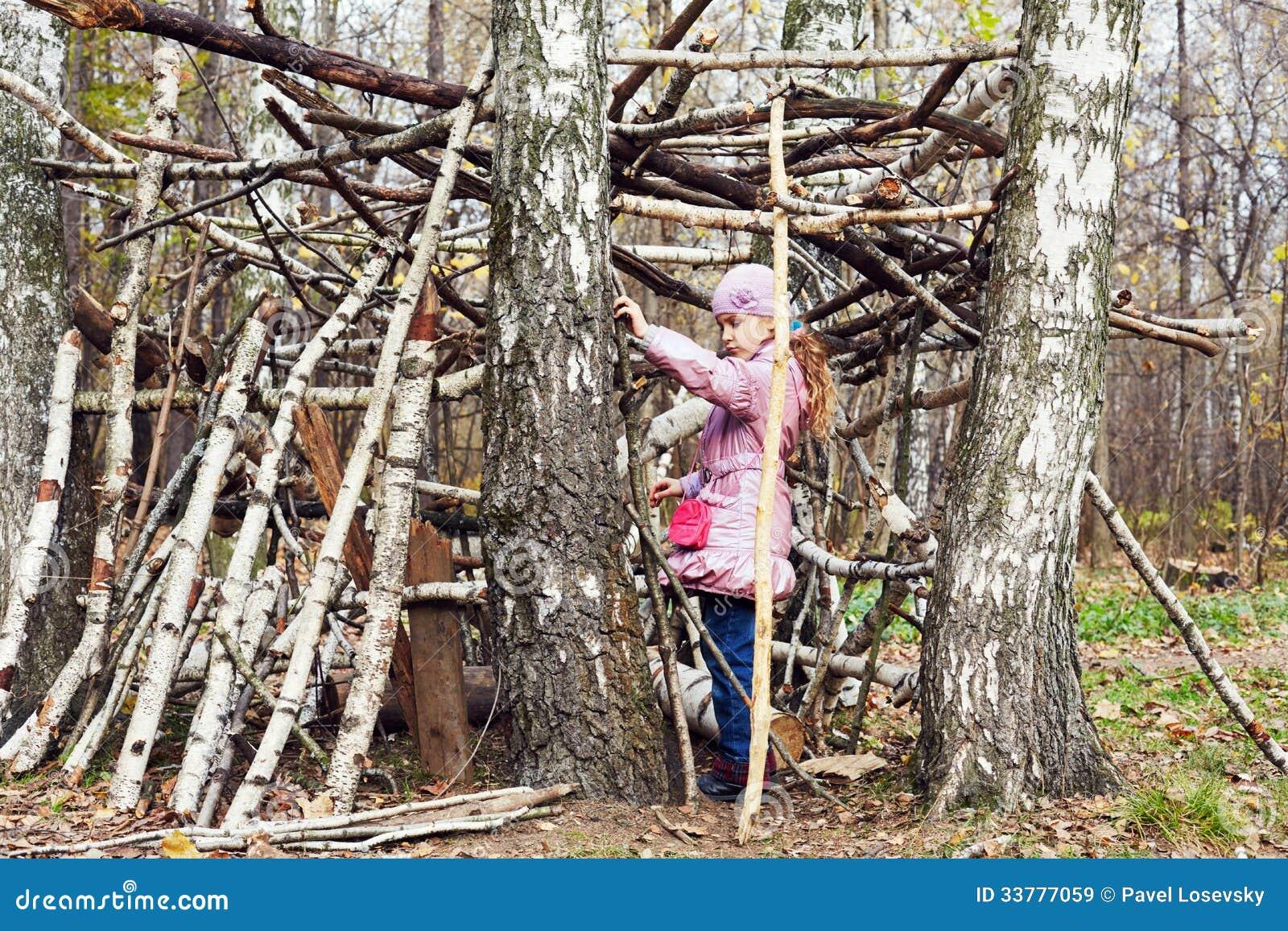 Το μικρό κορίτσι χτίζει την καλύβα μεταξύ των σημύδων