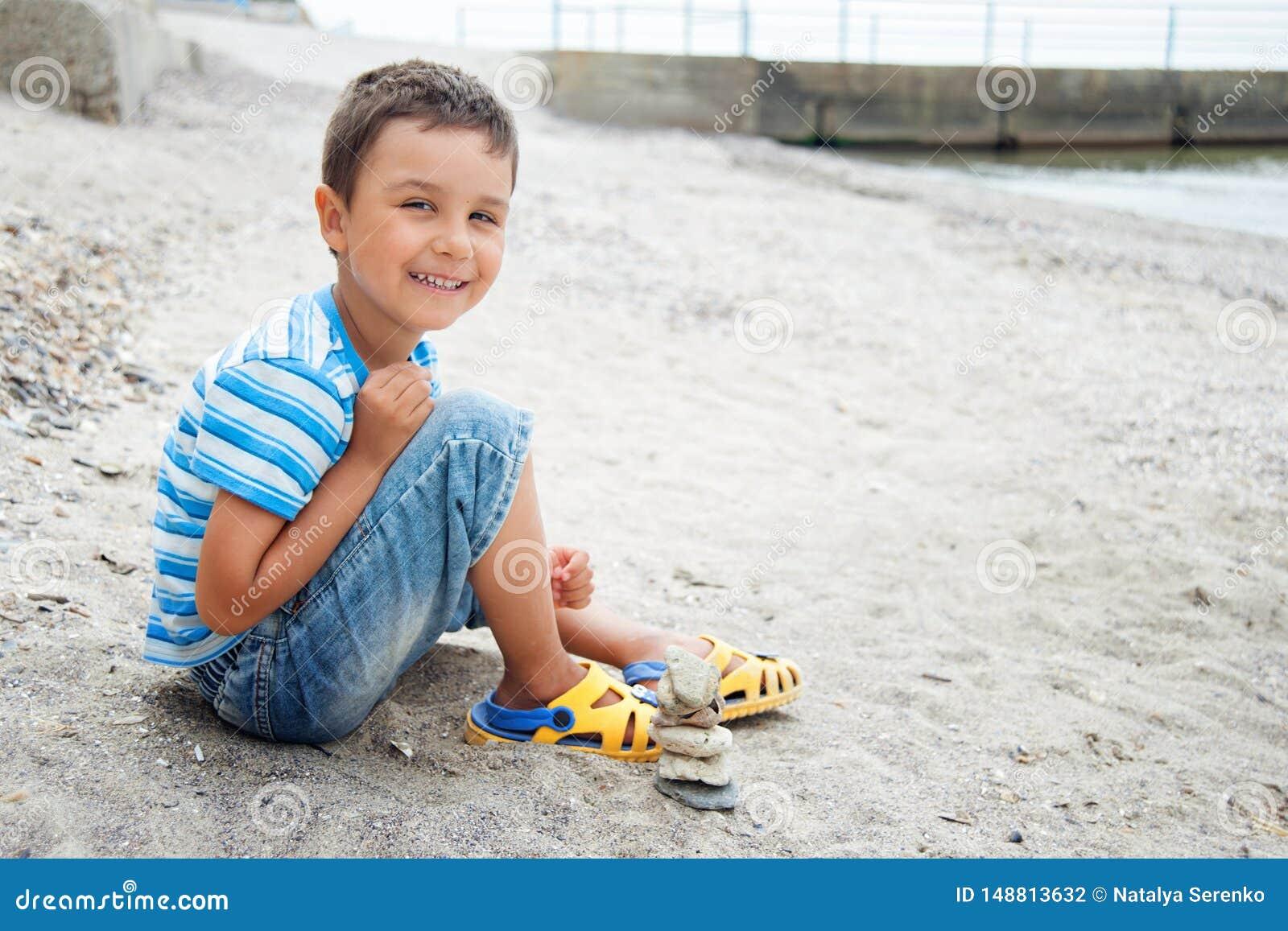το μικρό παιδί θαλασσίως συλλέγει τα θαλασσινά κοχύλια στην παραλία r E θερινές διακοπές εν πλω ή ωκεανός