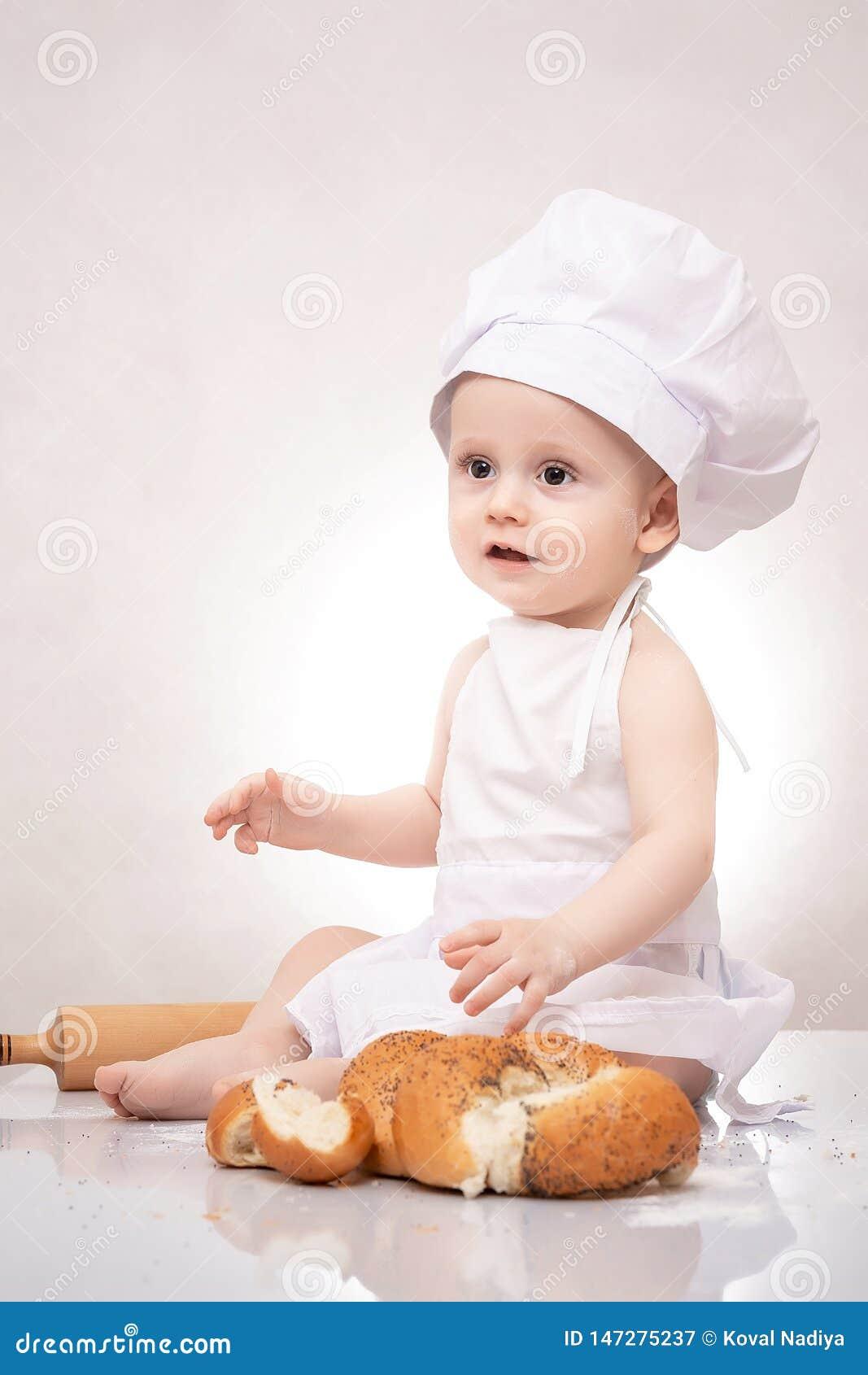 Το μικρό παιδί μαγειρεύει έναν croissant με το ψωμί να γελάσει ευτυχώς