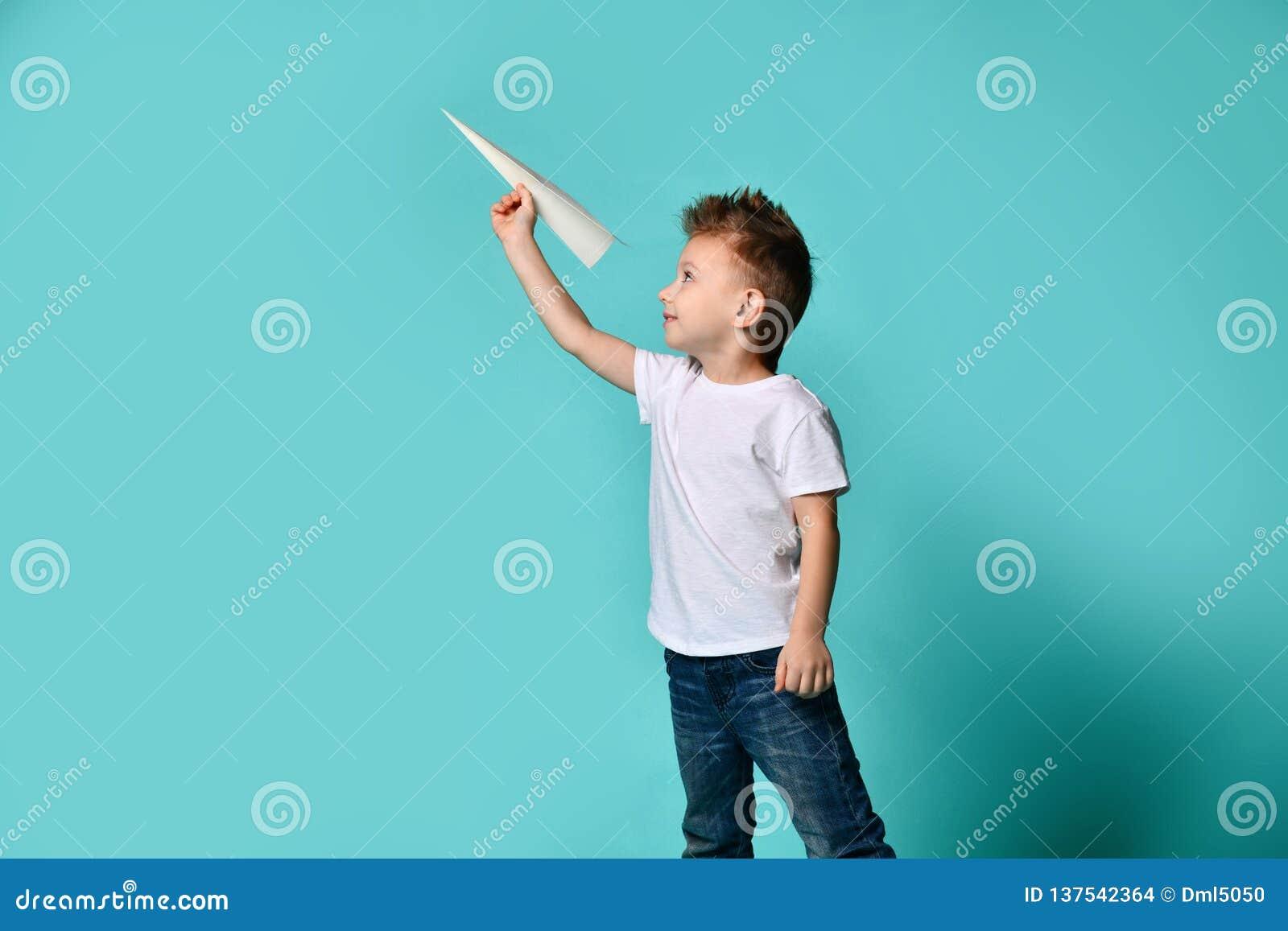 Το μικρό παιδί με το δροσερό παιχνίδι κουρέματος με ένα αεροπλάνο εγγράφου και εξετάζει το Παιδική ηλικία φαντασία