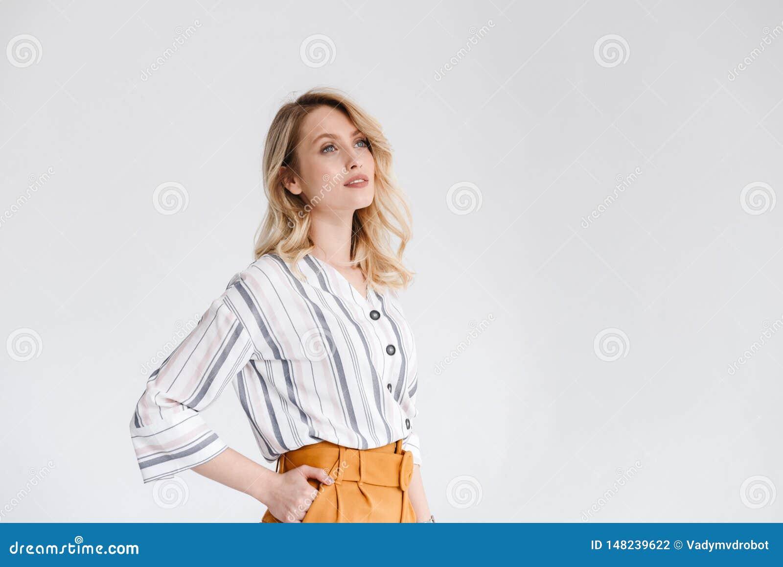 Το μισό πορτρέτο στροφής της νέας συμπαθητικής γυναίκας που φορά τα περιστασιακά ενδύματα που εξετάζουν κατά μέρος το copyspace μ