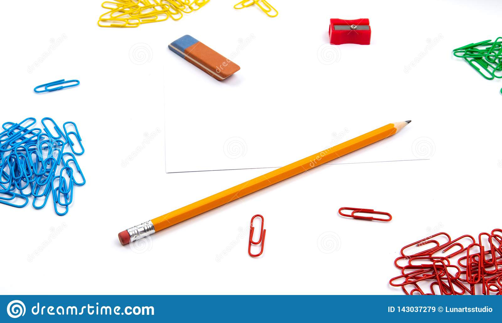 Το μολύβι, γόμα, sharpener, συνδετήρες εγγράφου βρίσκεται στις διαφορετικές γωνίες του φύλλου σε ένα άσπρο υπόβαθρο Εικόνα ηρώων