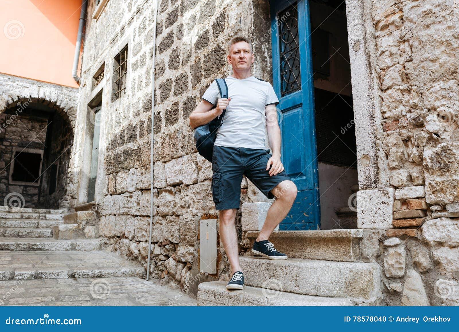d358a816543b Το μοντέρνο άτομο τουριστών έντυσε σε ένα άσπρο πουκάμισο και μπλε σορτς με  ένα μπλε σακίδιο πλάτης πέρα από τον ώμο του Στάση στα βήματα μιας παλαιάς  ...