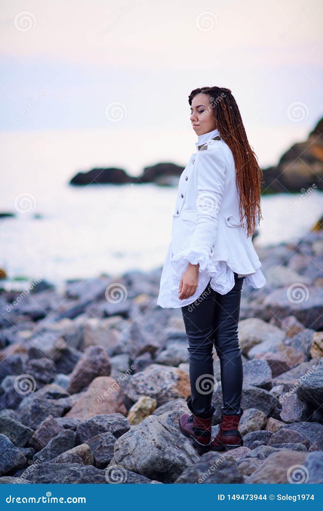 Το μοντέρνο κορίτσι Dreadlocks έντυσε στο άσπρο σακάκι και το μαύρο παντελόνι δέρματος που θέτουν κοντά στη θάλασσα το βράδυ