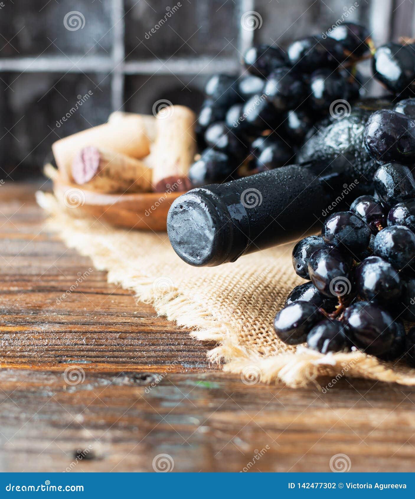 Το μπουκάλι του κόκκινου κρασιού με το φρέσκες σταφύλι και τη δέσμη βουλώνει στον ξύλινο πίνακα