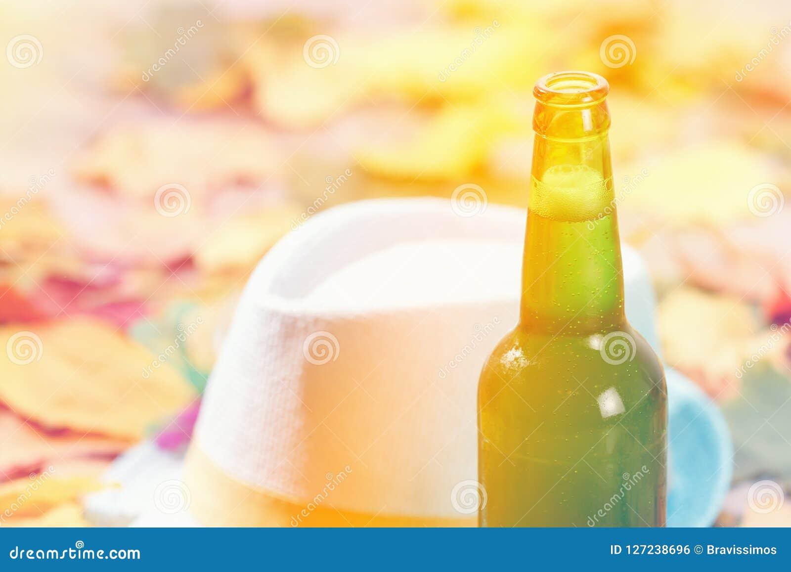 Το μπουκάλι του πιό octoberfest πικ-νίκ πιντών γυαλιού μπύρας στο φυσικό υπόβαθρο με το καπέλο και το φθινόπωρο φεύγει