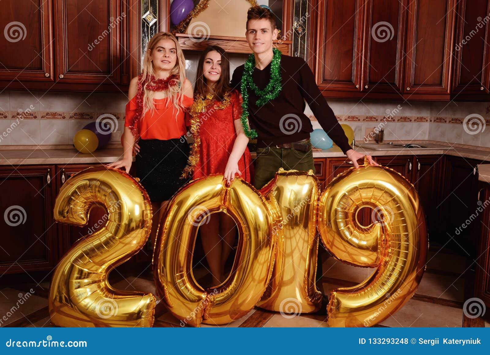 Το νέο έτος του 2019 έρχεται Η ομάδα εύθυμων νέων που φέρνουν τους χρυσούς χρωματισμένους αριθμούς και έχει τη διασκέδαση στο κόμ
