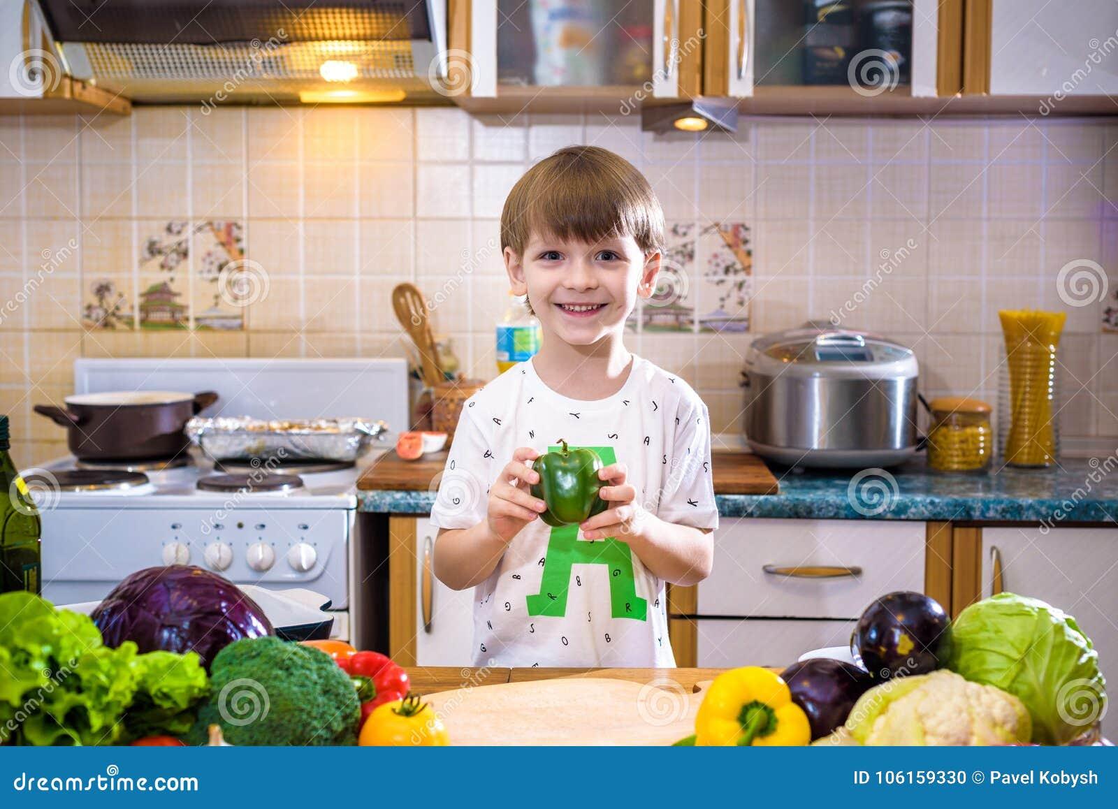 Το νέο αγόρι στο μαγείρεμα που στέκεται στην κουζίνα κοντά στον πίνακα με