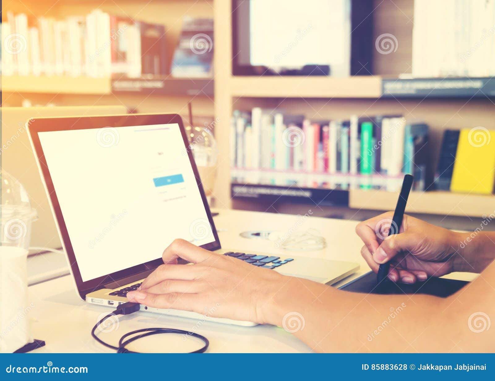 Το νέο γραφικό άτομο σχεδιαστών δίνει πολυάσχολο στη συνεδρίαση lap-top του στον πίνακα βιβλιοθηκών σε ένα πανεπιστήμιο